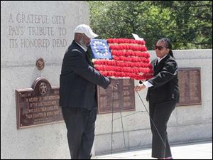 Toledo Mayor Mike Bell, left, and city council president Paula Hicks-Hudson with flowers for fallen veterans.