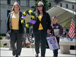 Gold Star Wives of America Sandra Hensley, of Holland, left, accompanies Veronica Mora and her son Topher Mora, 7, as they place a wreath during the ceremony. Topher is carrying photos of his late father, Sgt. Arthur Mora, U.S.Army.