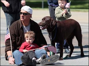 Todd Hagemeyer of Toledo, with his son Josh, 2, and dog Moses. At right, standing, is Roger Phillips, 4, also of Toledo.
