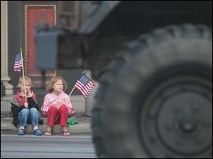 Joshua, 4, left, and Rebekah Childress, 9, of Toledo watch as an Army vehicle moves past.