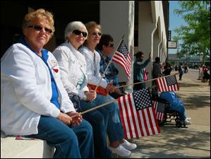 Watching the parade along Summit Street are, from left and front: Sandy Lyell, Pam Brenneman, Betty Solener, and her sister-in-law Cindy Solener, all of Toledo.