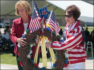 Heroes in Action members Kim Sheehan, left, and Dawn Heisler, both of Toledo, carry a wreath to place at the memorial site.