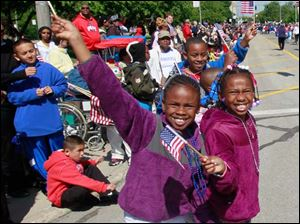 Danaiya Witcher, 7, left, and her sister Danijha, 8, along the parade route.
