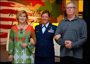 Teresa Fedor, left, and Jeff Lever, right, escort Air Force veteran Jen Bauer as she is announced at the Dancing with the Military Stars event.
