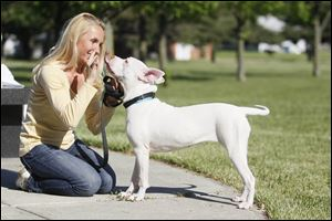 Angi Holt-Parks teaches Rudi, who is deaf,  to kiss her by signing the word 'love' at Friendship Park Community Center.