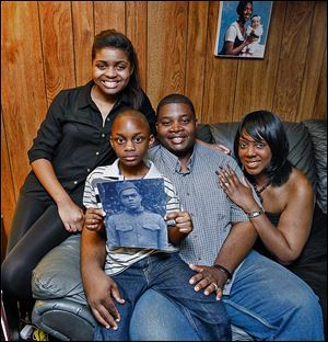 The Quinn family, from left Braniya, 15; Braylin, 7, and parents Anthony and Brandi, show a portrait of Homer Lee Quinn, Anthony's great uncle who died serving in the Army.
