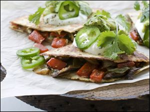 Mushroom, pepper and onion quesadillas are shown in Concord, N.H. Full-fat cheese is the secret to a flavorful recipe.