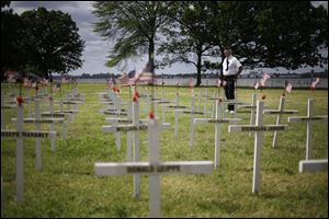 Bob Lewis looks over a field of crosses with names while participating in the College Point Memorial Day Parade in New York, Sunday. Lewis made the crosses, 137, for all the service members from College Point that were killed from the Civil War to the Vietnam War.
