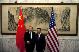 U.S. National Security Adviser Tom Donilon, left, and Chinese State Councilor Yang Jiechi, right, shake hands before their meeting at Diaoyutai State Guesthouse in Beijing, China, today.