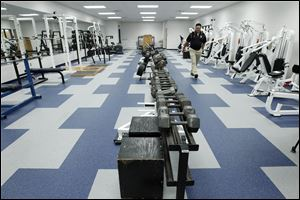 Eric Hirzel, school board vice-president walks through the weight room during a tour of the new Lake High School on August 1, 2012.