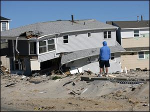 A man looks at damaged homes on  Fort Avenue in Ortley Beach, N.J., Sunday. While parts of New Jersey's shore has made great progress over the past seven months, towns still have a long way to go to recover from Superstorm Sandy.