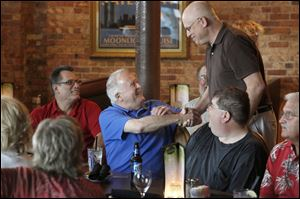 Peter Cavanaugh, center, greets Mark Benson during a dinner and reunion of local radio broad-casters at Manhattan's Restaurant in the Uptown district. Mr. Cavanaugh, a member of the Rock and Roll Hall of Fame and former Toledo radio broadcasting exec, put together the reunion.