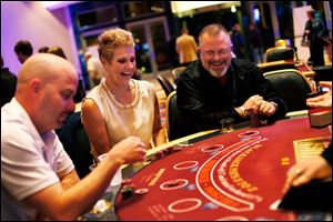 Temperance, Mich. residents Chris and Paul Szymanski, center and right, smile as they play blackjack along with Chicago, Ill. resident Shane Engels.