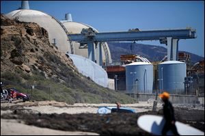 Surfers walk along a beach nearby the San Onofre Nuclear Power Plant in San Onofre, Calif.