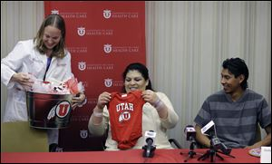 Dr. Tracy Manuck, left, gives a baby present to Guillermina and Fernando Garcia today after  a news conference at the University of Utah hospital, in Salt Lake City.