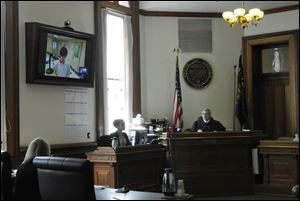 Grant Alan Acord, 17, upper left, is seen in a video feed from where he is being held on a television screen as Judge Matthew Donahue, right, speaks to lawyers today at the Benton County Courthouse in Corvallis, Ore.