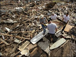 Friends and family members carry what remains of piano through the rubble at a tornado-ravaged home, in Moore, Okla.,  Saturday.