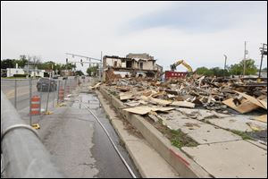 The demolition underway of the old Colony shopping center at the corner of Monroe Street and Central Avenue.