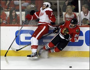 Detroit Red Wings defenseman Carlo Colaiacovo (28) and Chicago Blackhawks left wing Viktor Stalberg (25) collide during the third period in Game 7 of the NHL hockey Stanley Cup Western Conference semifinals.