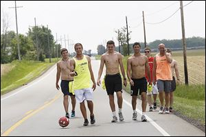 Derek Garde, left, Nick Streibick, center left, Isaac Beal, center, and Jake Essig, center, right, walk along U.S. 127 near Fulton County's Fayette on the 11th day of their walk, Thursday. The four are kicking a soccer ball along a 250-mile route. They call themselves Dribble 4 Toledo.