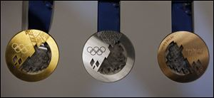 Gold, left, silver, center, and bronze medals are displayed for journalists during a presentation of Sochi 2014 Olympic medals at the SportAccord International Convention today in St. Petersburg, Russia.