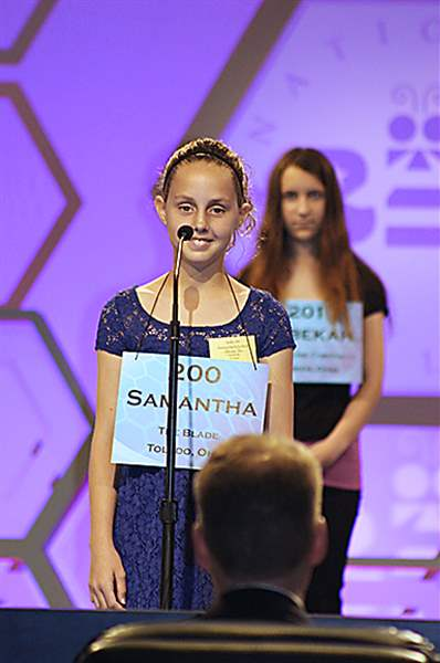 Samantha-Schofield-stands-on-stage-as-she-spells-the-word