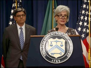 Treasury Secretary Jacob Lew, left, listens at left as Health and Human Services Secretary Kathleen Sebelius speaks about Social Security and Medicare, today, at the Treasury Department in Washington.