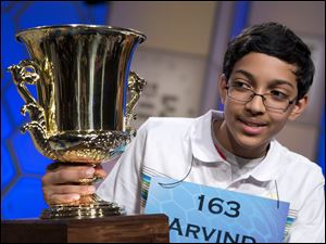 "Arvind Mahankali, 13, of Bayside Hills, N.Y., holds the championship trophy after he won the National Spelling Bee by spelling the word ""knaidel"" correctly on Thursday."