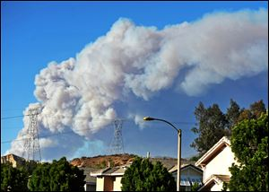 Smoke from the Powerhouse Fire is visible from the Saugus neighborhood of Santa Clarita, Calif.