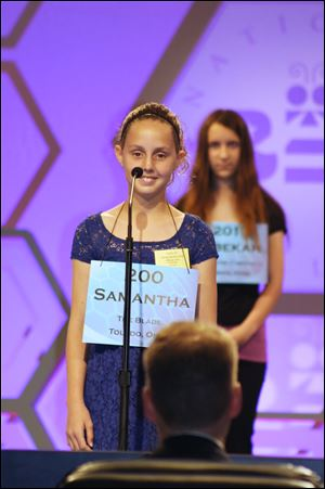 Samantha Schofield stands on stage as she spells the word 'amphibious' in the National Spelling Bee on Wednesday.