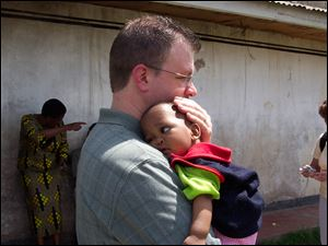 Bryan, Ohio resident Mark Holbrook holds the young African boy he and his wife plan to adopt later this year.