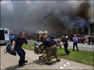 A firefighter is wheeled to an ambulance after fighting a fire at the Southwest Inn, Friday in Houston. A fire that engulfed a motel killed four firefighters.