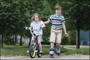 Siblings Wren Rausch, 8, right, and Lucy Rausch, 6, left, race down the sidewalk in front of their house on Princeton Dr. while playing outside on May 22, 2013.