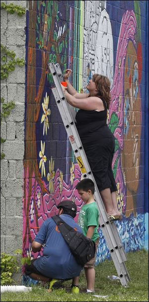 Jennifer Jacobs, the CEO of the Providence Center, helps paint the mural on the exterior walls of the center on Broadway Street.