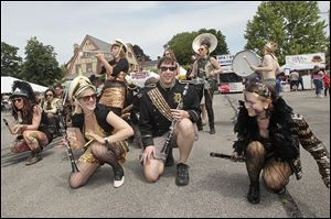 Crouching, from right, Taylor Kozak, Alex Pritchard, and Antha Ann, all of Detroit, swing and squat as they and other members of the Detroit Party Marching Band perform.
