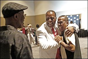 Kenny Cunningham, center, greets Bobby Clay of Omaha at the City League basketball reunion at SeaGate Convention Centre.