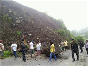 Rresidents look at boulders that partially blocked a highway after an earthquake in North Cotabato in southern Philippines Sunday.