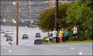Shawna Block (in yellow) runs along Johnson Ferry Road in Marietta, Ga.