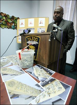 A bucket of mushrooms sits on a table as Toledo Police Chief Derrick Diggs speaks during a September press conference. Toledo's internal crime statistics are markedly different than those reported to the FBI in 2012 and 2011. And the numbers in the police department's annual report last year differ from those presented to city council in an April 16 memo written by Chief Diggs.