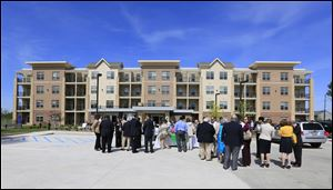 Dozens turn out for the dedication of the first phase of the $46 million Collingwood Green Senior Community at Division and Belmont in central Toledo on Tuesday. Residents can move in June 24.