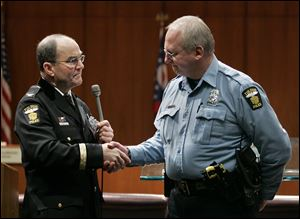 Officer Robert Adams, right, is presented with badge No. 1 by then Toledo Police Chief Mike Navarre during a Toledo police department promotions ceremony in February, 2010.