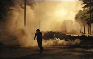 A protester runs to avoid tear gas during clashes with the police in Istanbul early today.