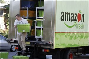 An Amazon Fresh worker delivers groceries in Seattle, where the ecommerce giant has deployed a fleet of 12 trucks to test its new service.  Customers also can pick up grocery orders at certain sites.