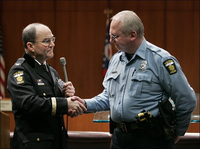 CTY promotions18p 05 adams, navarre 2010 Officer Robert Adams, right, is presented with badge No. 1 by then Toledo Police Chief Mike Navarre during a Toledo police department promotions ceremony in February, 2010.
