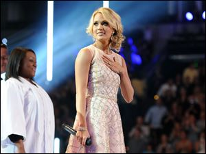 Carrie Underwood pauses on stage at the 2013 CMT Music Awards at Bridgestone Arena in Nashville, Tenn.