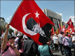 A Turkish protester waves a national flag with a poster of Turkey's founder Kemal Ataturk as thousands of trade union members who are on a two-day strike march to Kizilay Square, city's main center, in Ankara, Turkey, today.