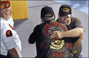 Marine Corps veteran Roy Hernandez, back right, is hugged by Army veteran John Pernia, of Toledo during the Honor Roll Call portion of the event, which drew nearly 200 Vietnam-era vets.