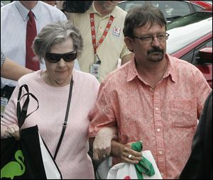Powerball winner Gloria C. Mackenzie, 84, leaves the lottery office escorted by her son, Scott Mackenzie, after claiming a single lump-sum payment of about $370.9 million before taxes today in Tallahassee, Fla.