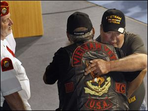 Marine vet Roy Hernandez, back right, is hugged by Army veteran John Pernia, of Toledo.