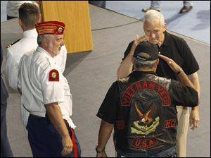 Marine vet Roy Hernandez, back right, is saluted by Army veteran Larry Hall, of Toledo.